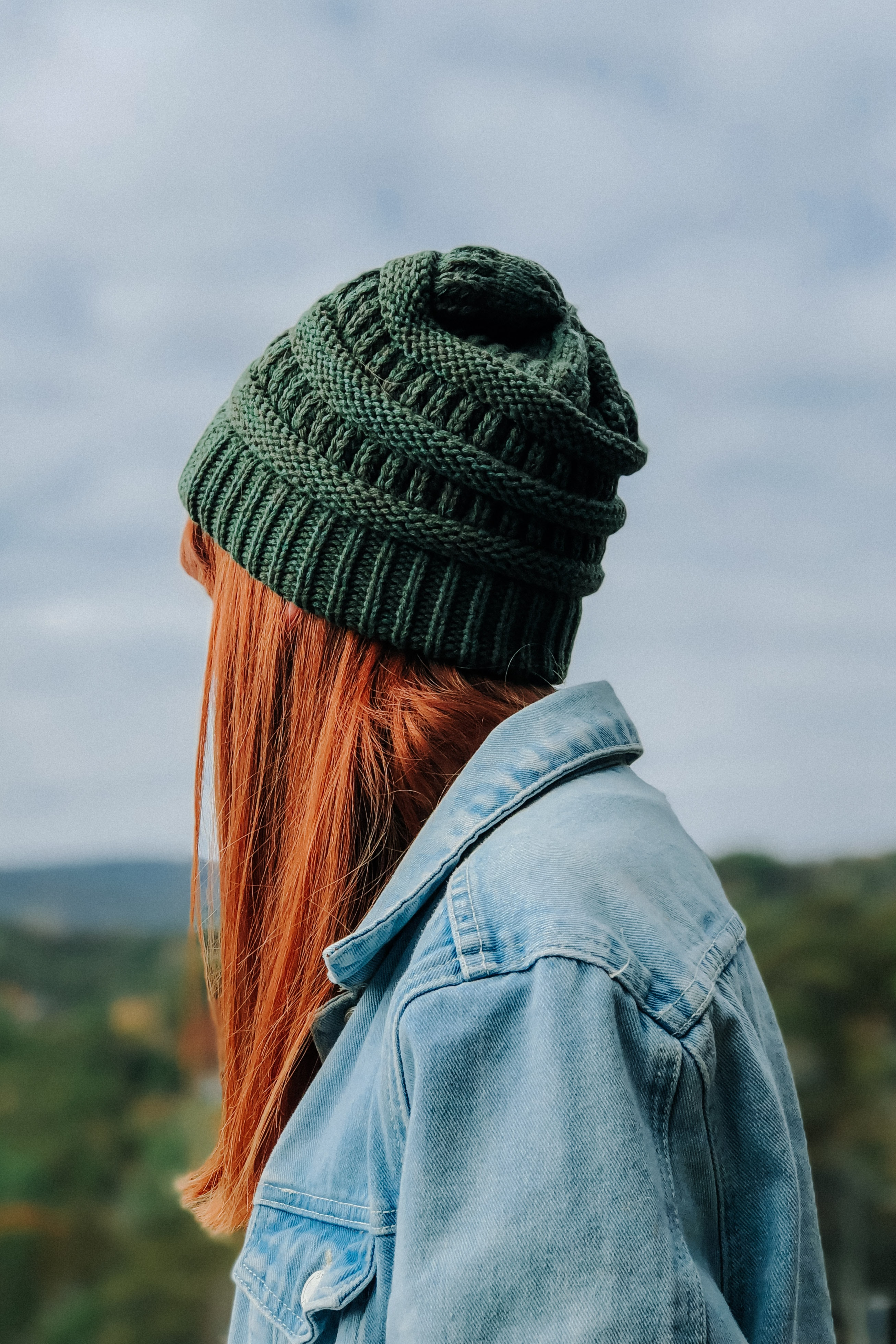 woman wearing green knit cap and blue denim jacket