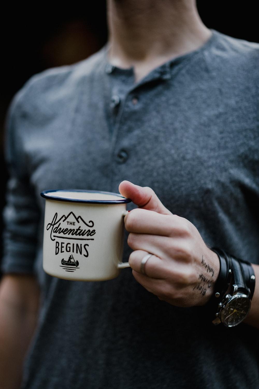 man holding white ceramic mug