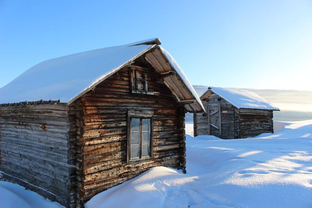 two wooden houses covered snow during daytime