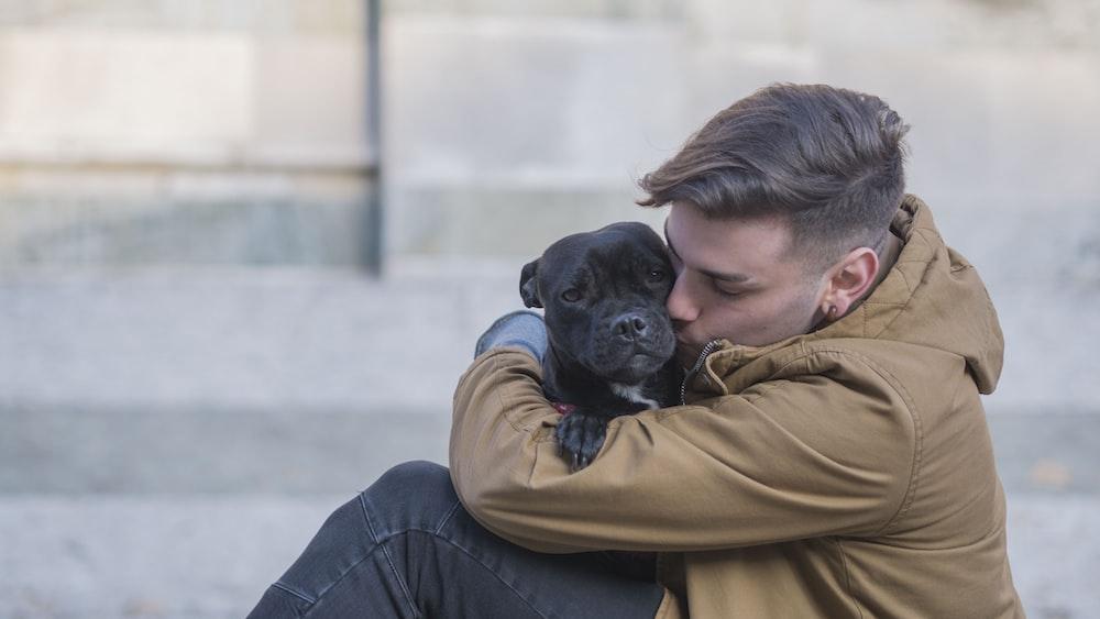 selective focus photography of man hugging black dog