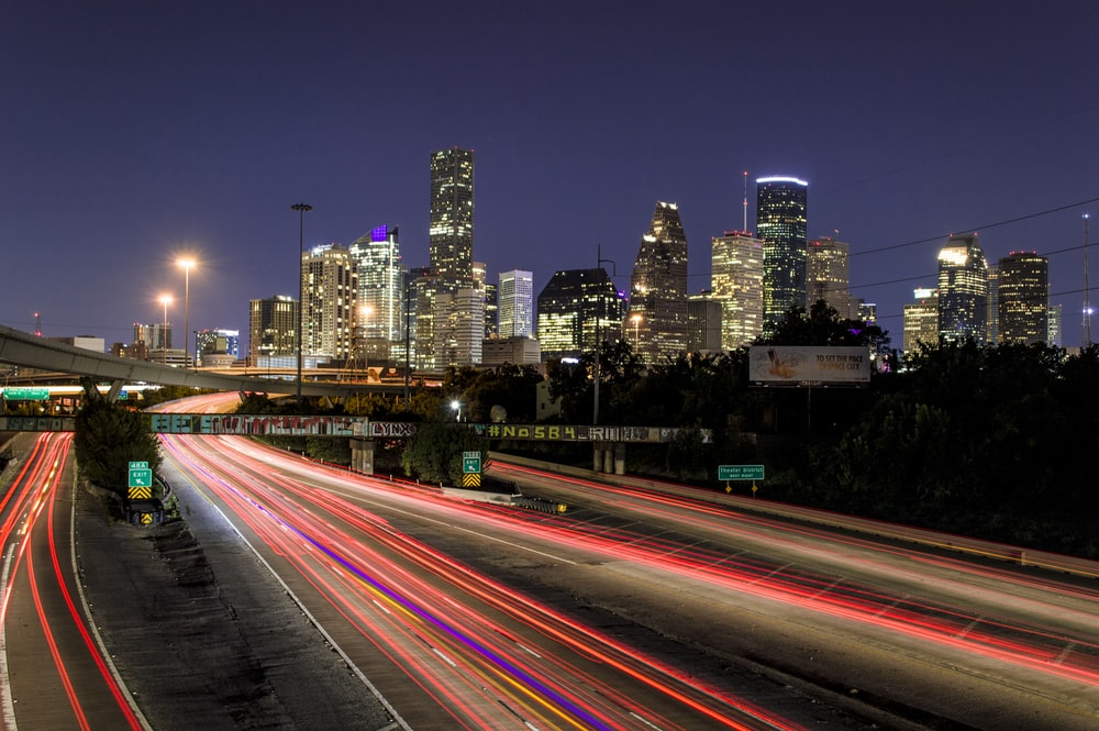 time lapse photography of vehicle traveling with a speed of light in road