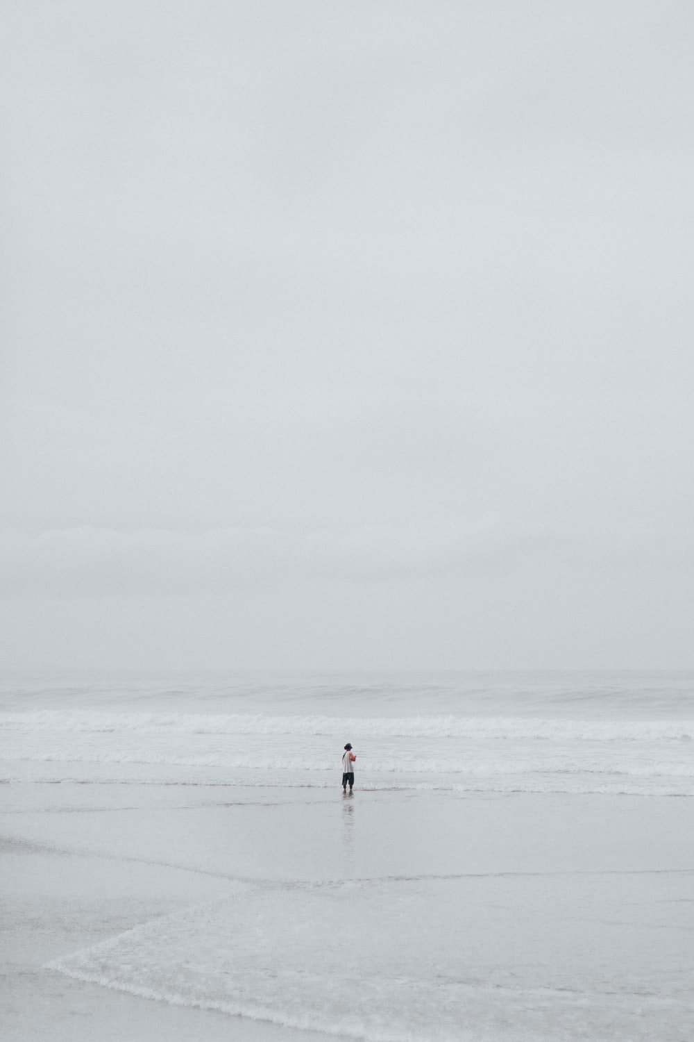 person in middle of seashore