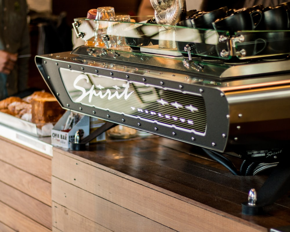 focus photography of Spirit Triplette machine on top of wooden counter