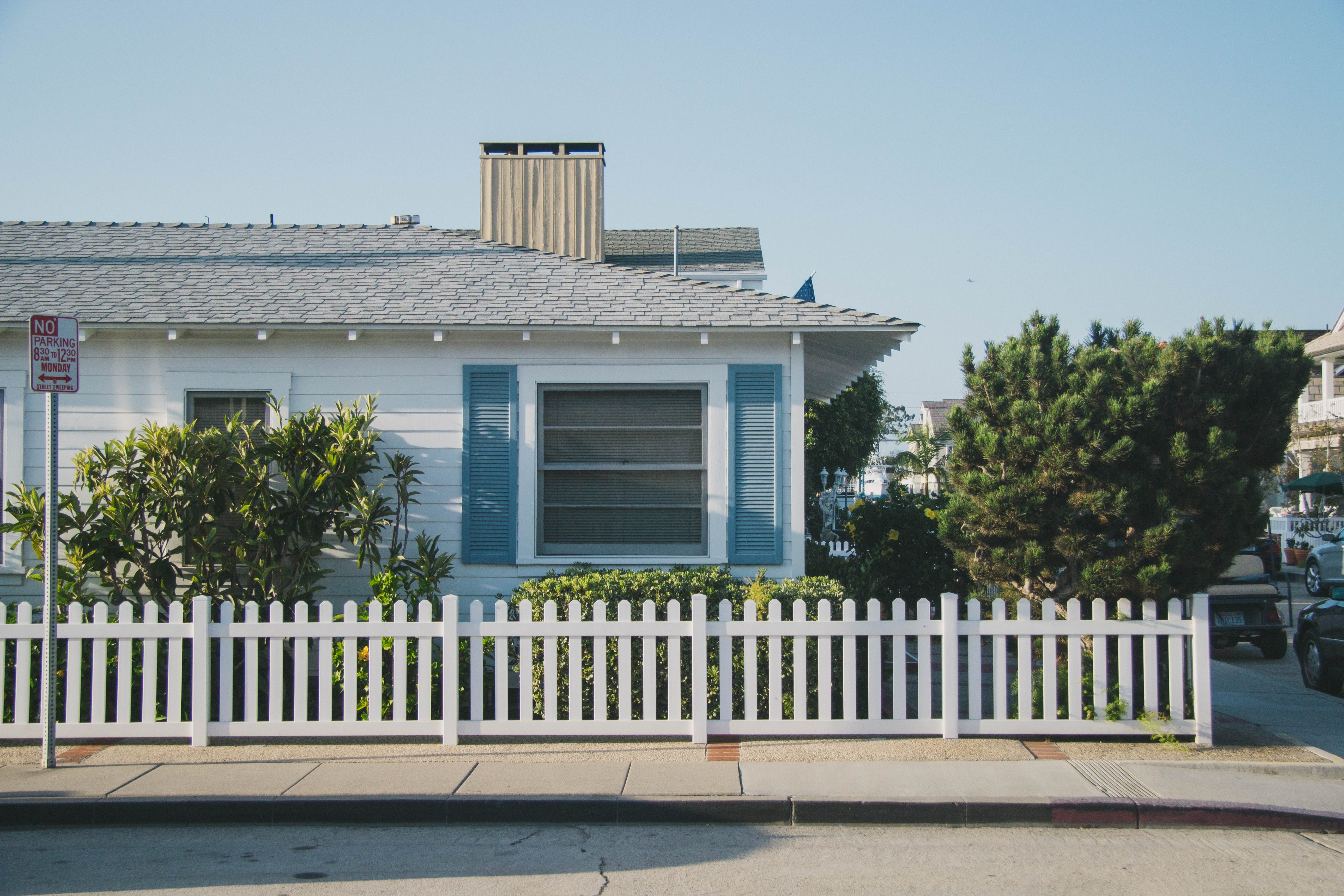 white and blue house beside fence