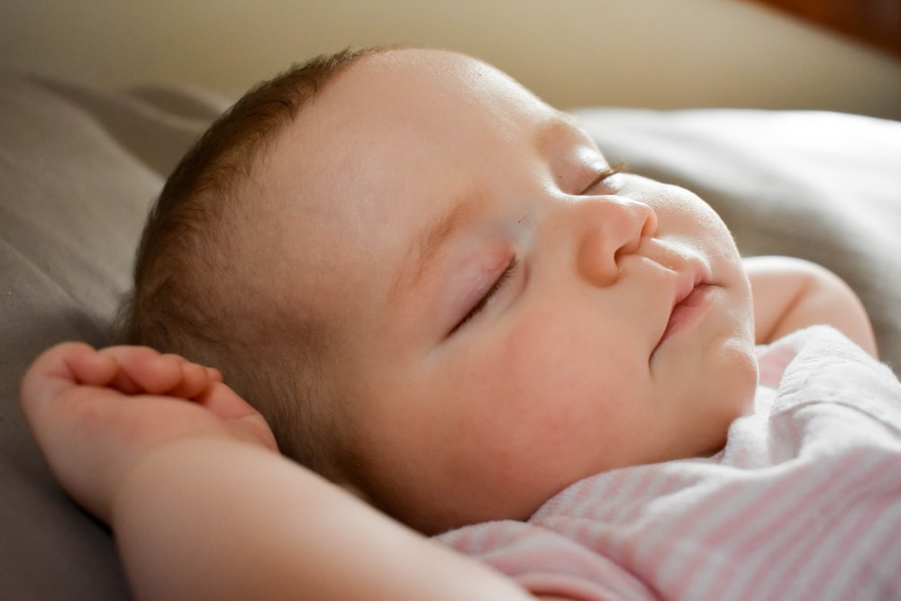 sleeping baby on gray cushion