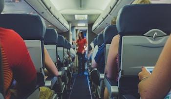 flight attendant standing between passenger seat