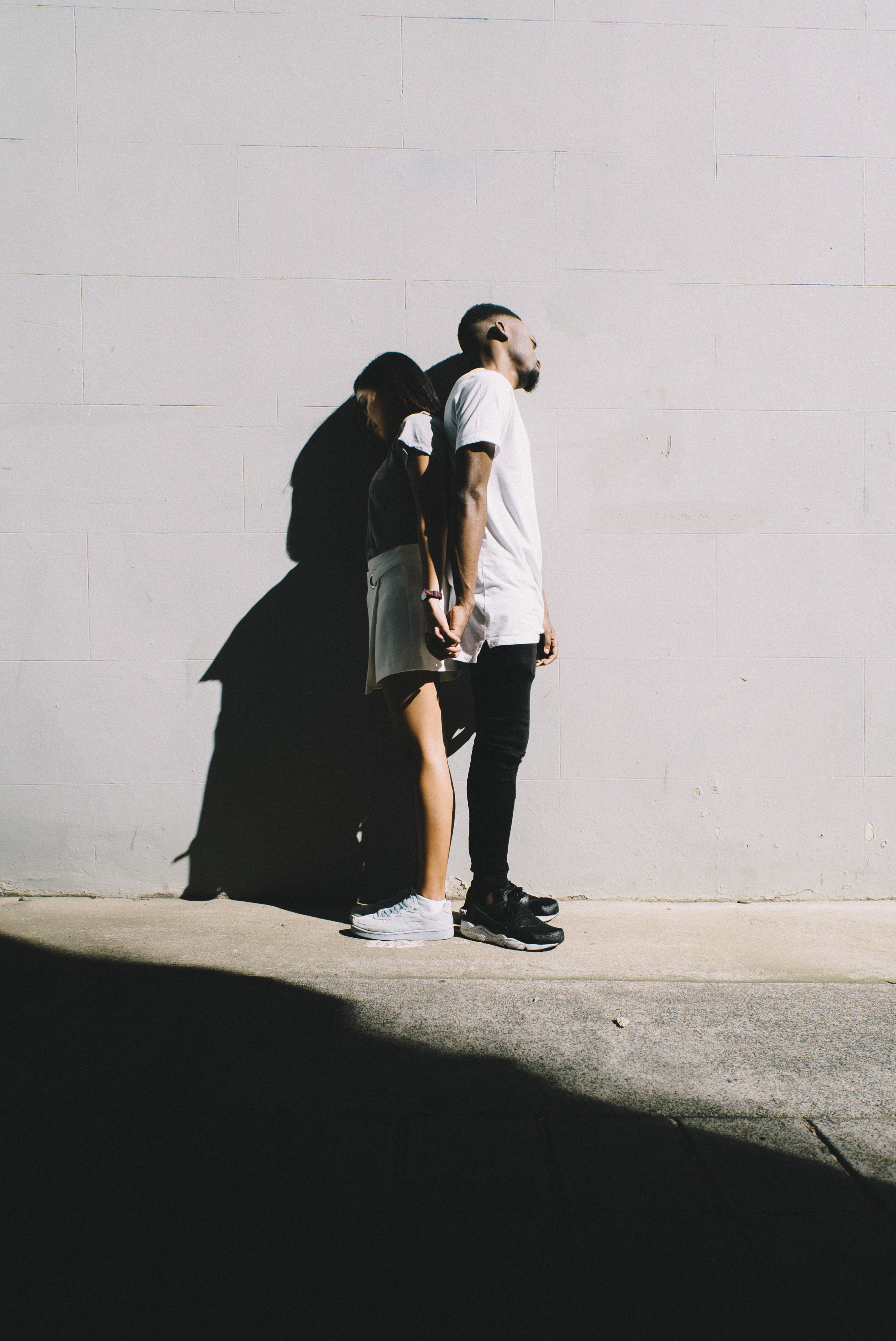 couple leaning on wall