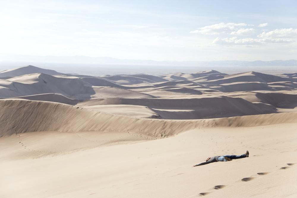 man lying on desert at daytime