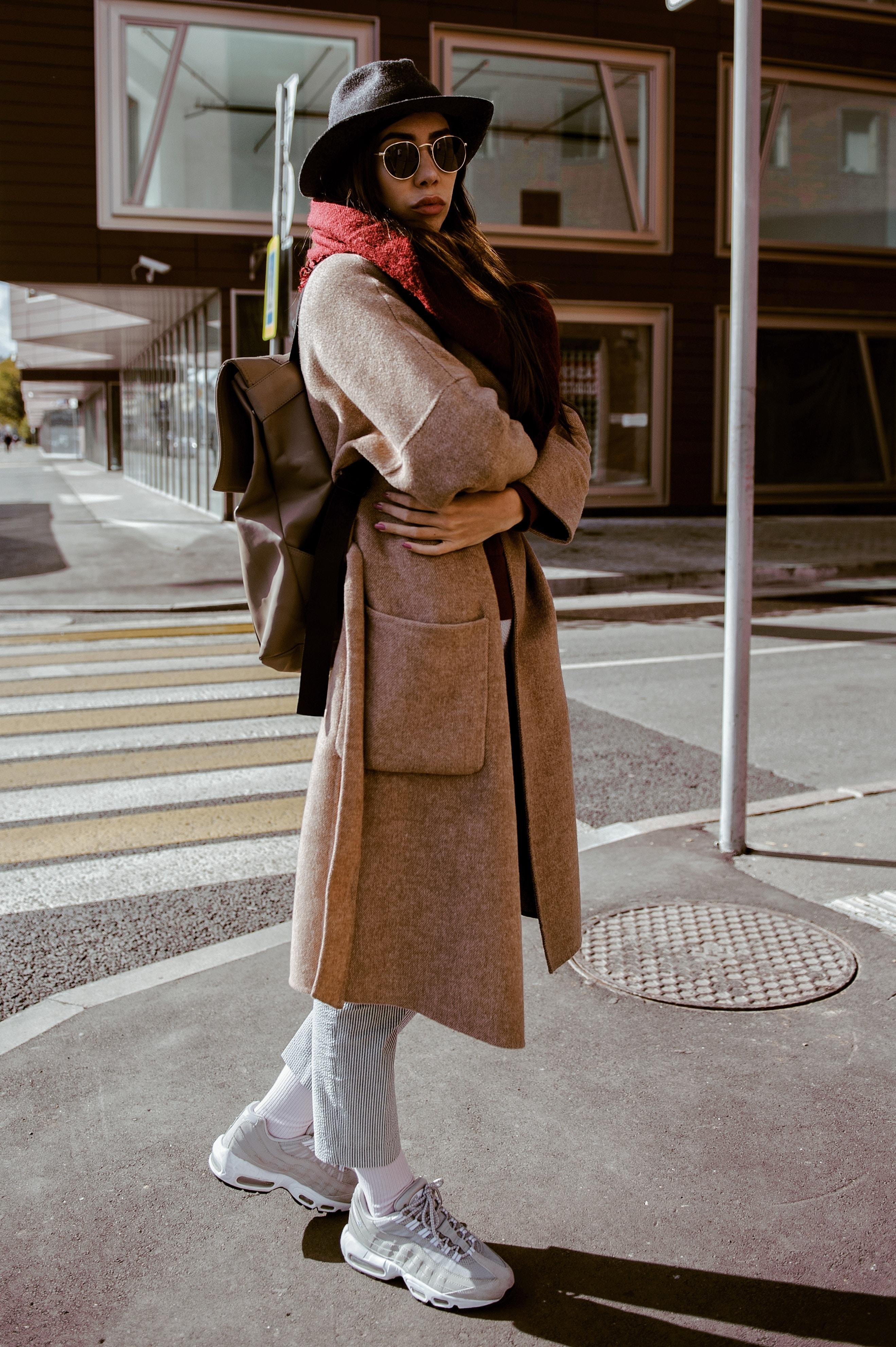 woman in brown coat near pedestrian during daytime