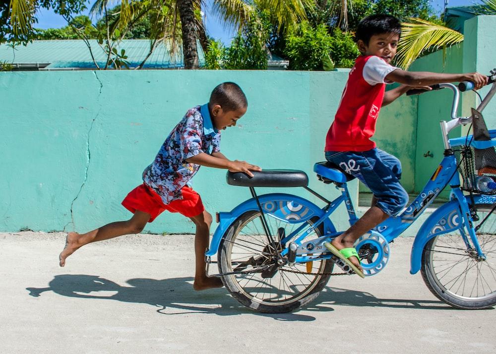 boy cycling near green wall during daytime