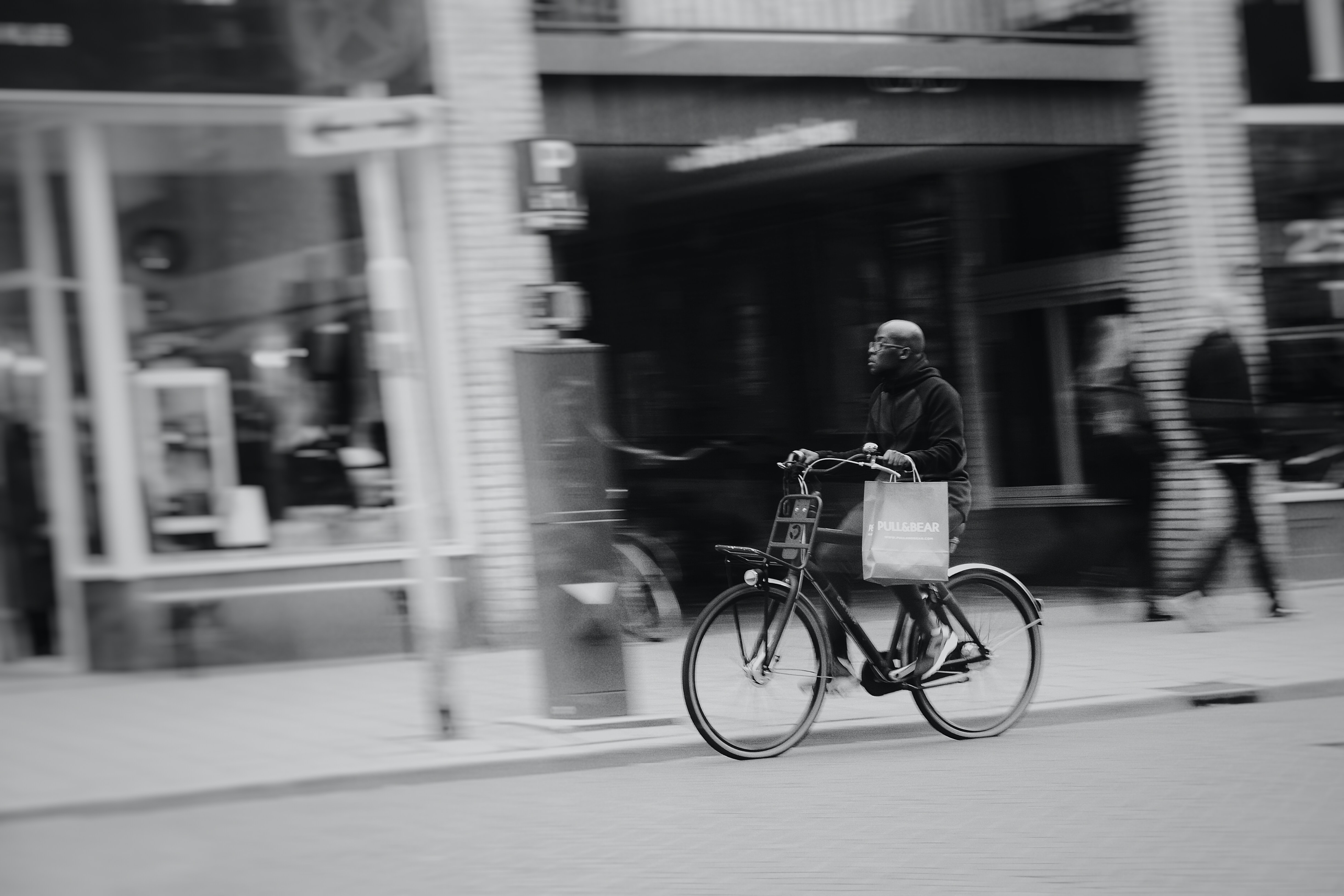 man riding bicycle on road near stores