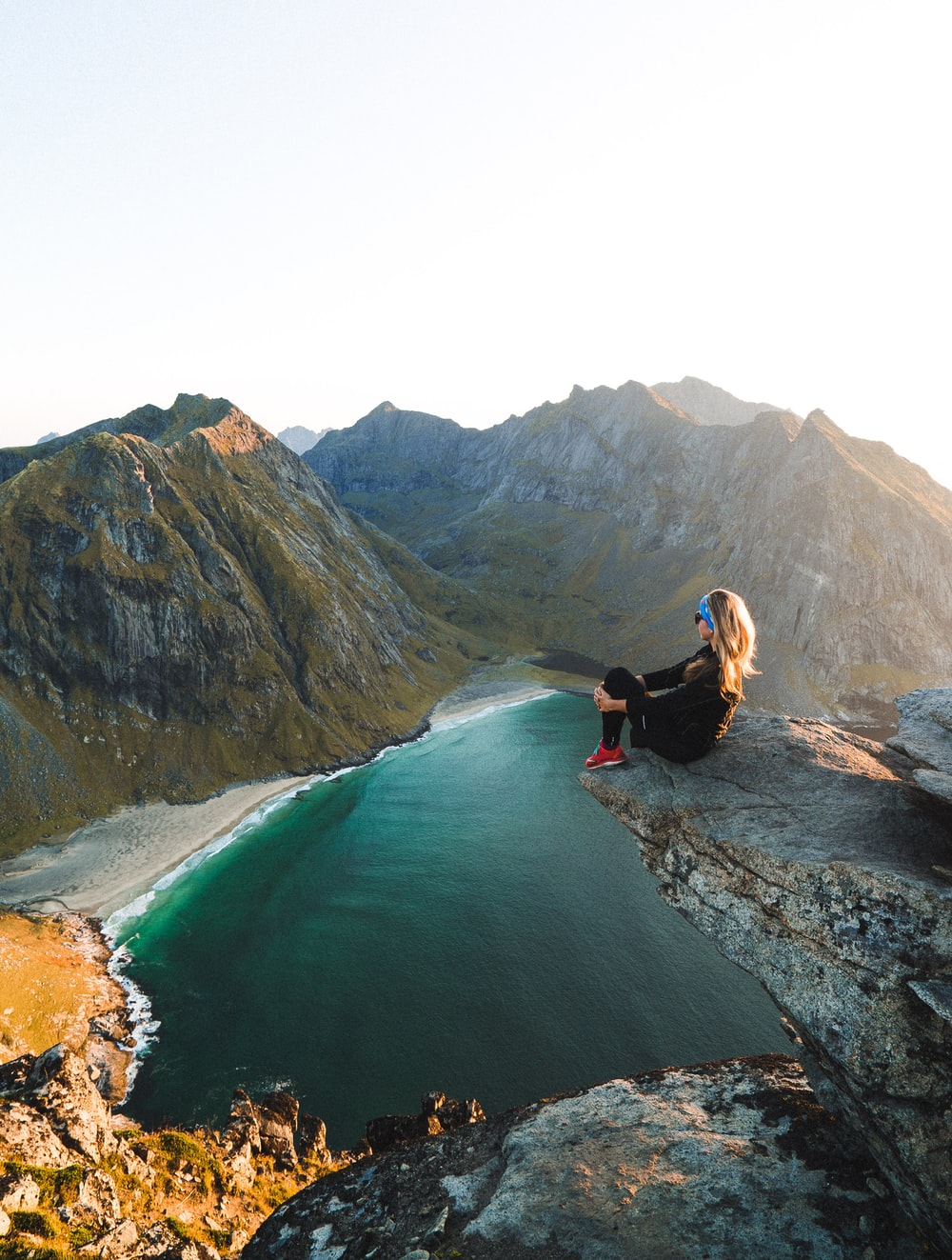 woman sitting on cliff overlooking body of water near mountains during daytime