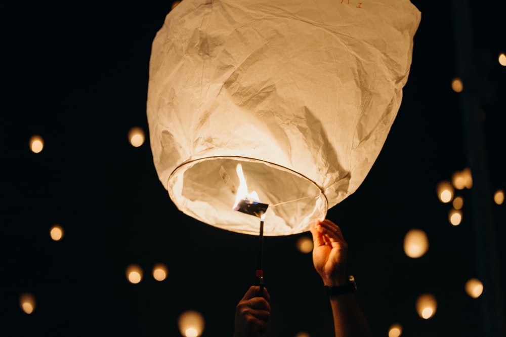 person holding sky lantern at night