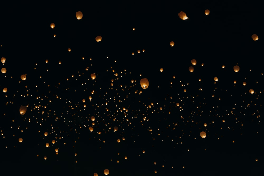 floating paper lanterns on sky during nighttime