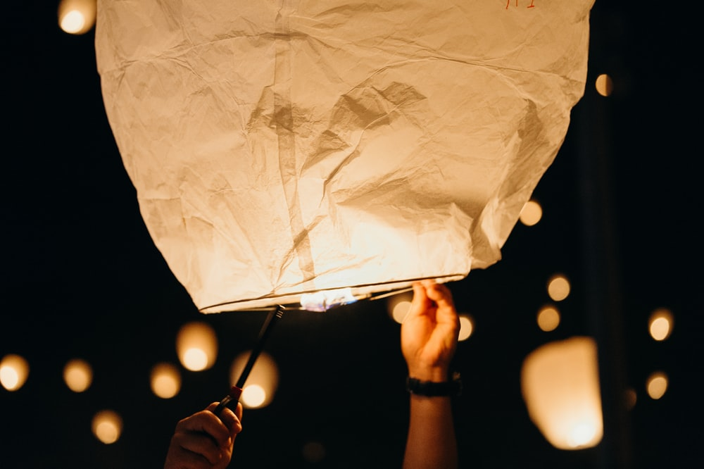 white paper lantern flying at nighttime