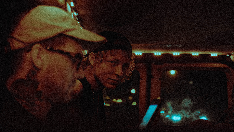 man wearing cap beside man at nighttime
