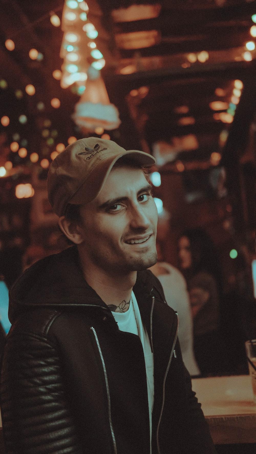 man wearing black jacket smiling inside brown room