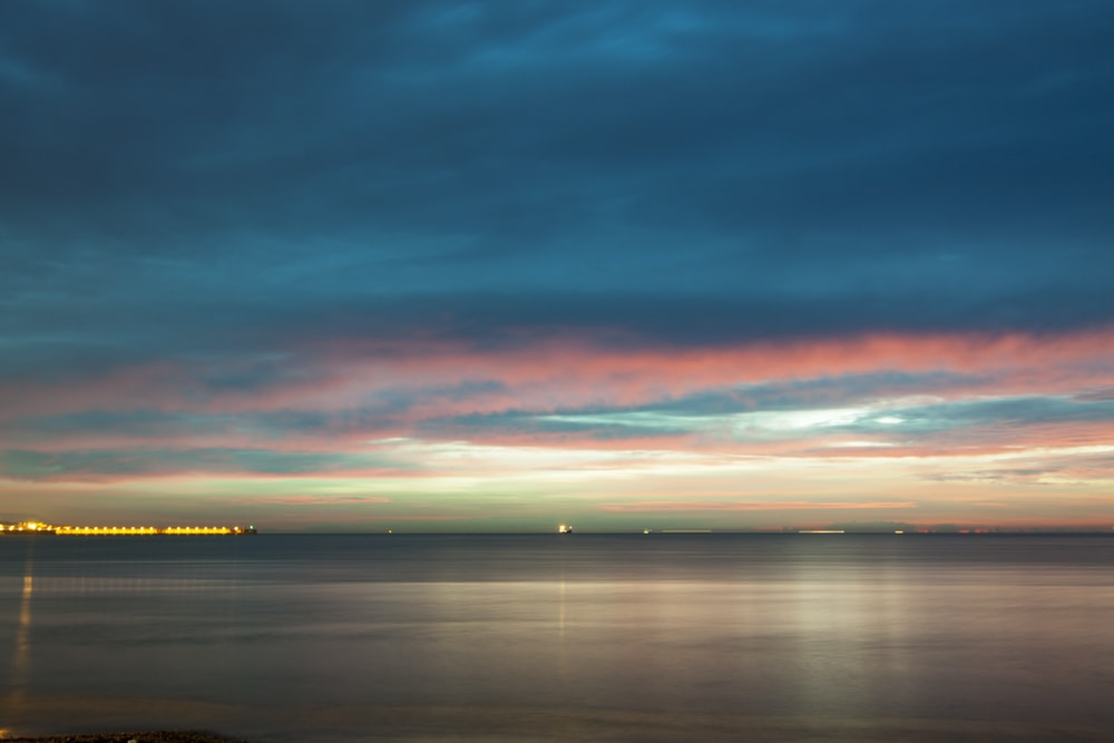 panoramic photography of calm waters over blue skies