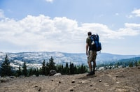 man hiking on brown mountain while carrying blue hiking bag