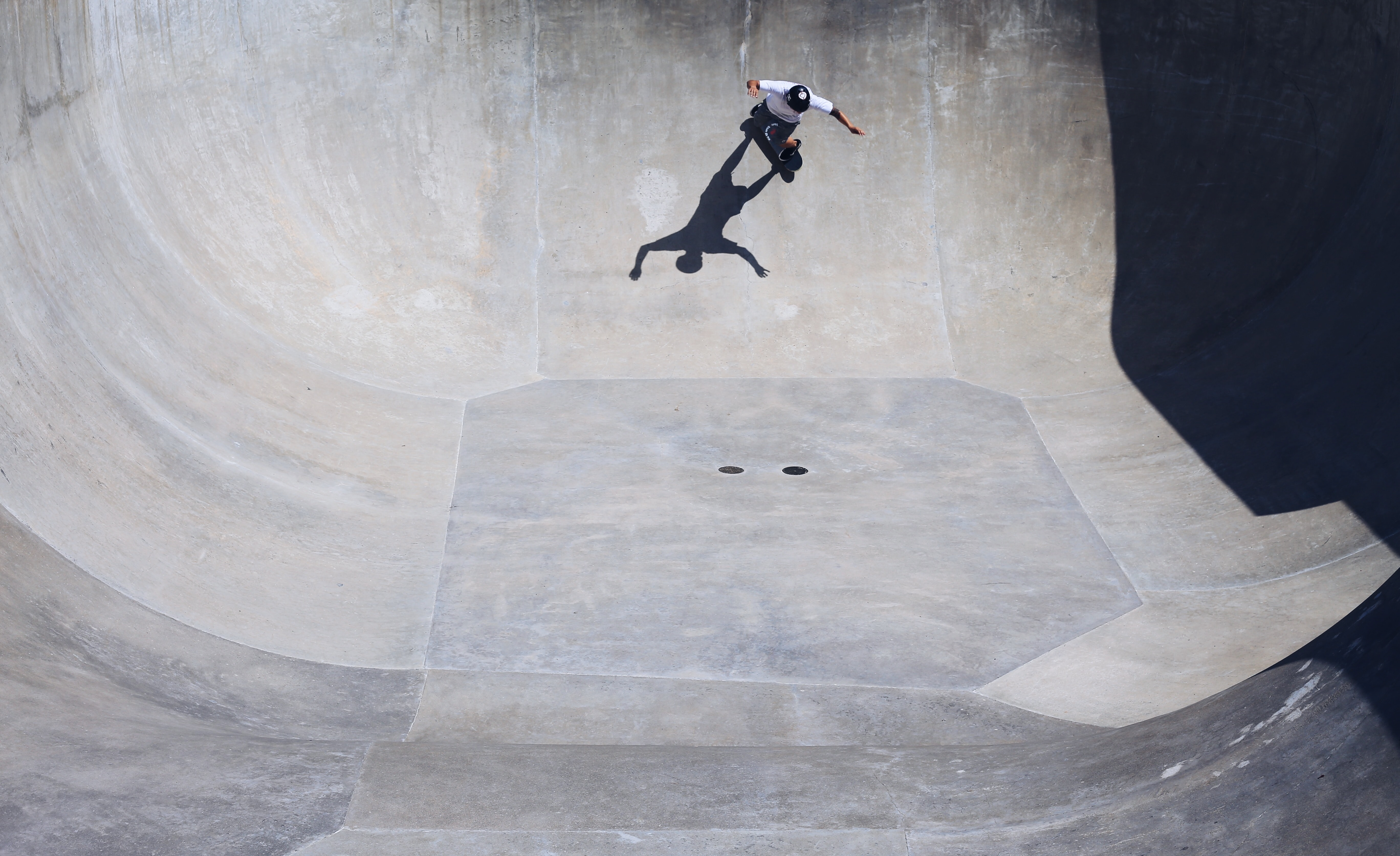 man wearing white t-shirt riding on a skateboard playing on the giant half bowl