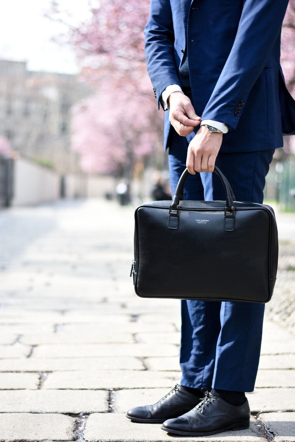 man in blue suit standing on street side while holding bag during daytime