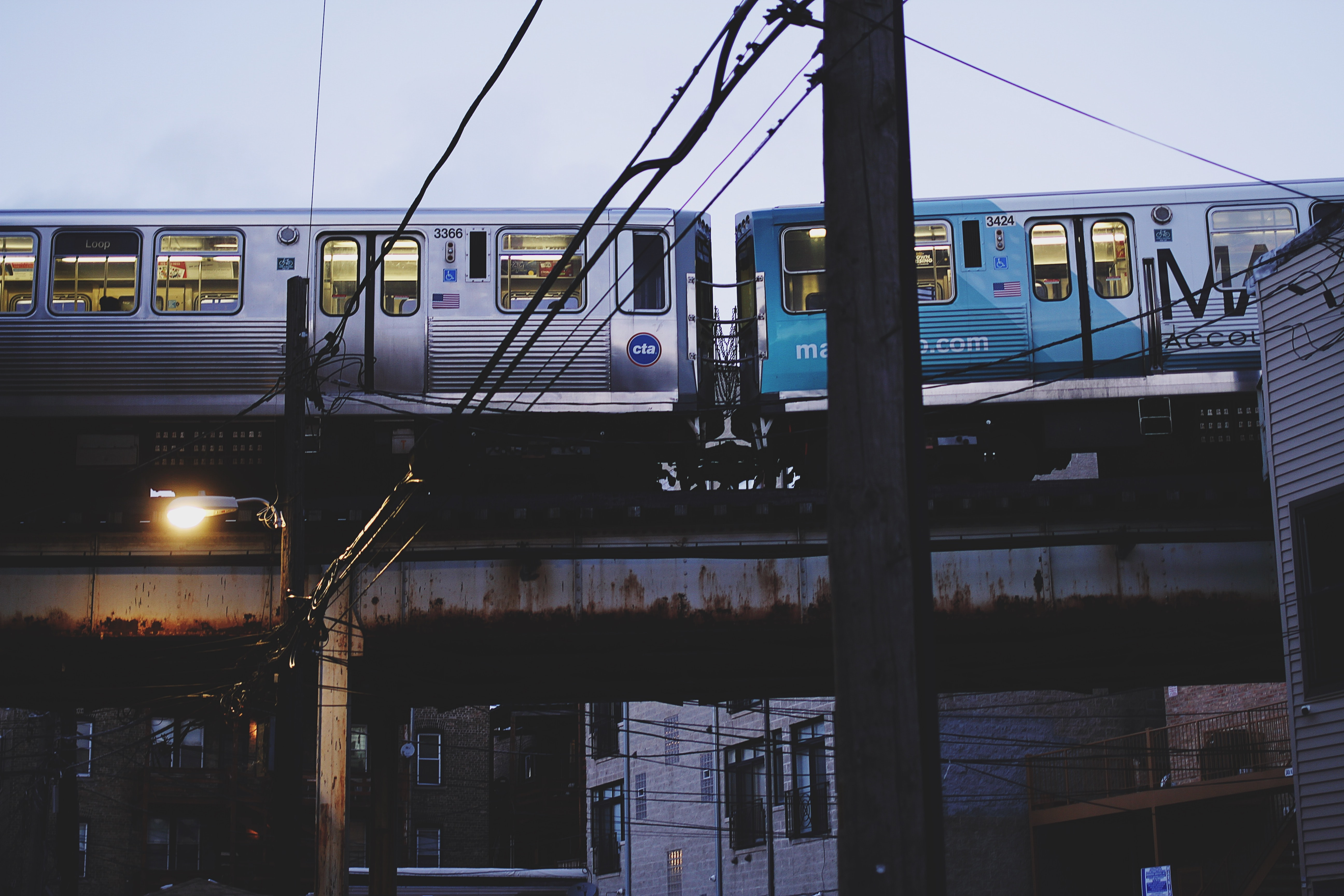 two gray and blue trains under white sky