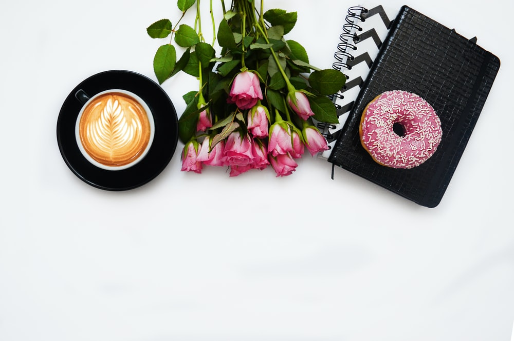 red rose flowers, pink dough nut graphic book and black ceramic cup