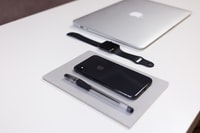 jet black iPhone 7 and MacBook Air on white table