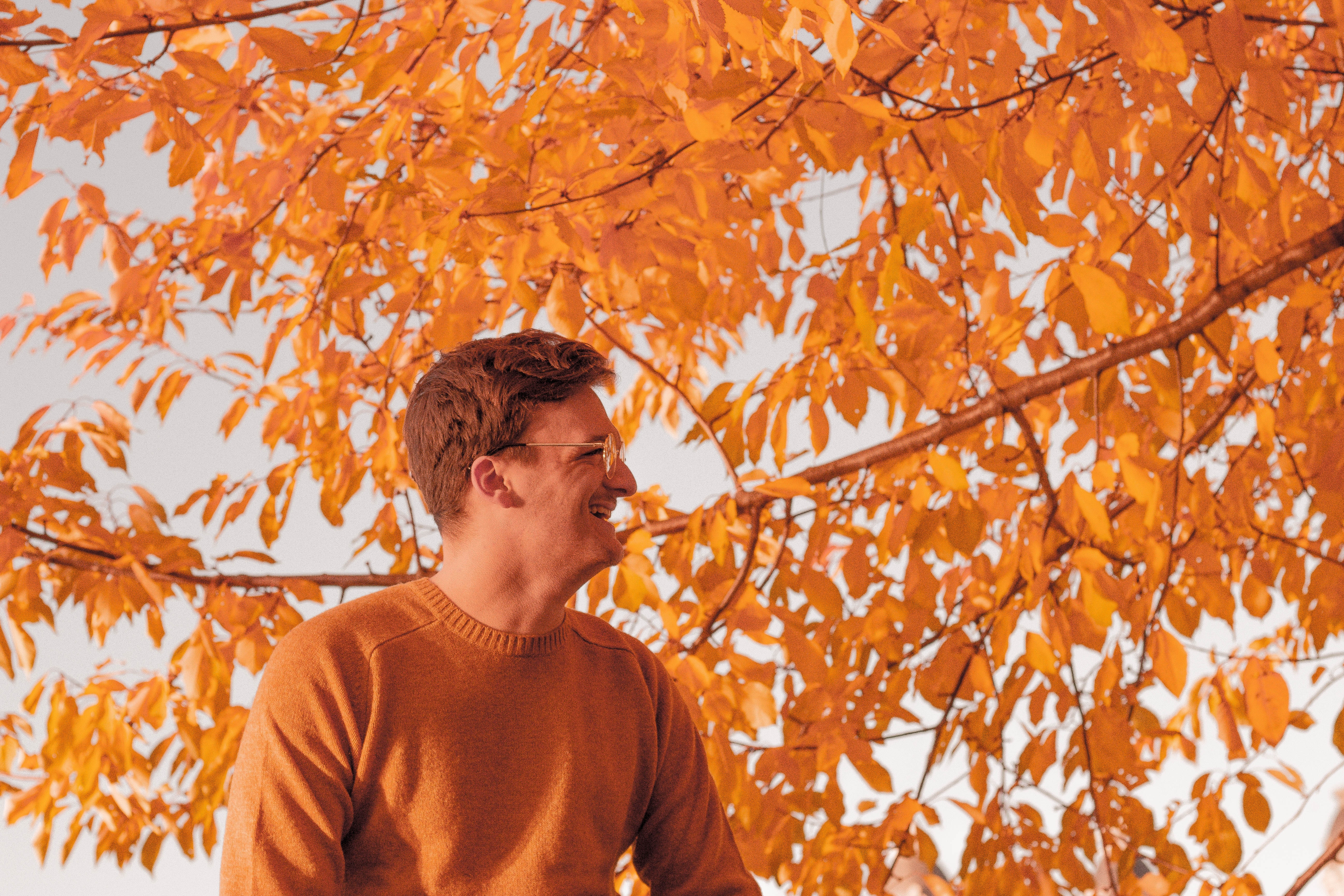 man standing in front of brown leaf tree