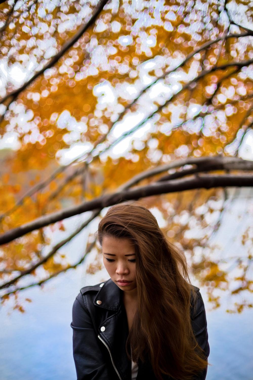 woman wearing black leather jacket under orange leafed tree during daytime