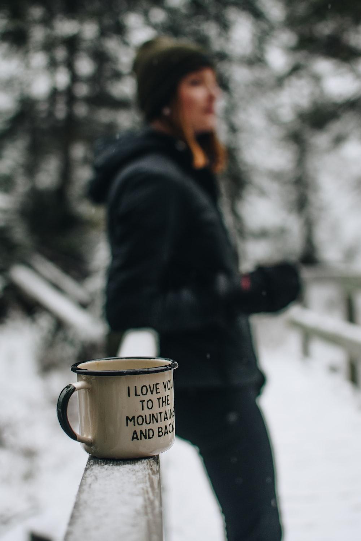 white and black glass mug on brown wooden handle bar