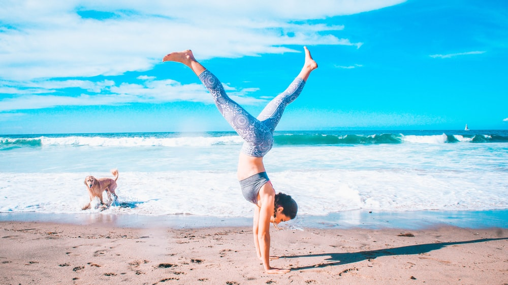 woman performing inverted stand beside seashore