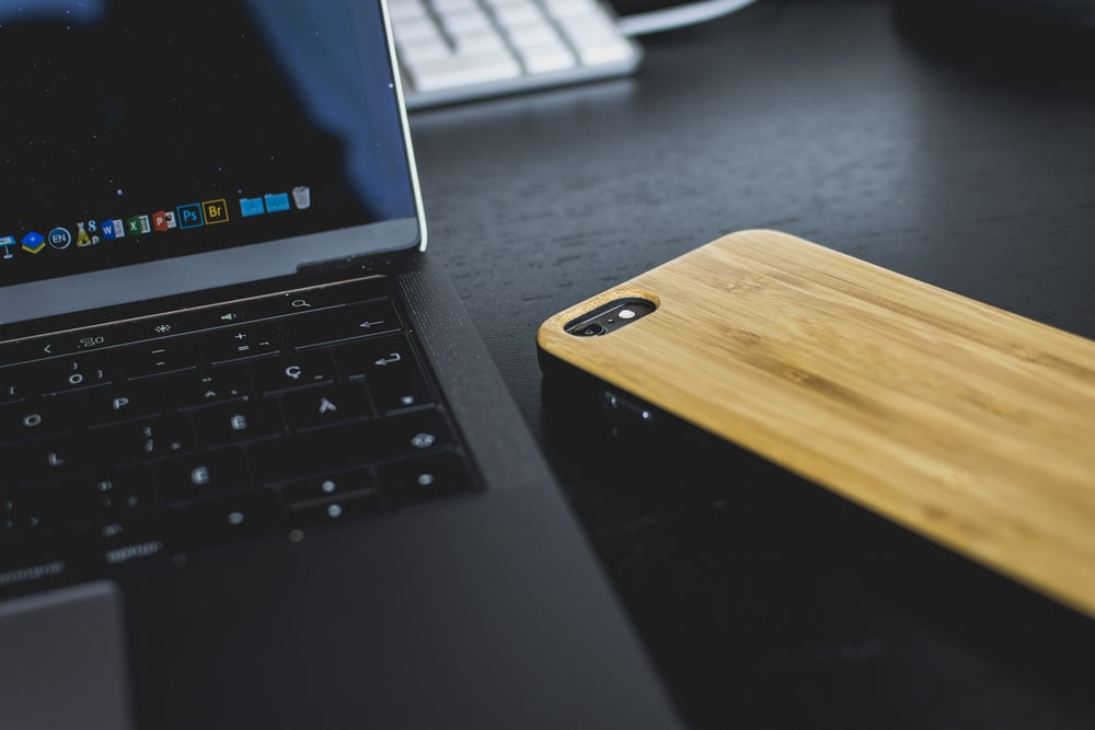 brown wood-style iPhone case near laptop computer