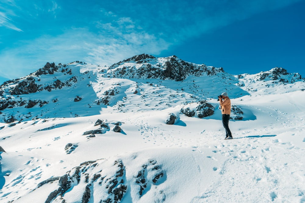 person taking picture on top of snow covered mountain during daytime