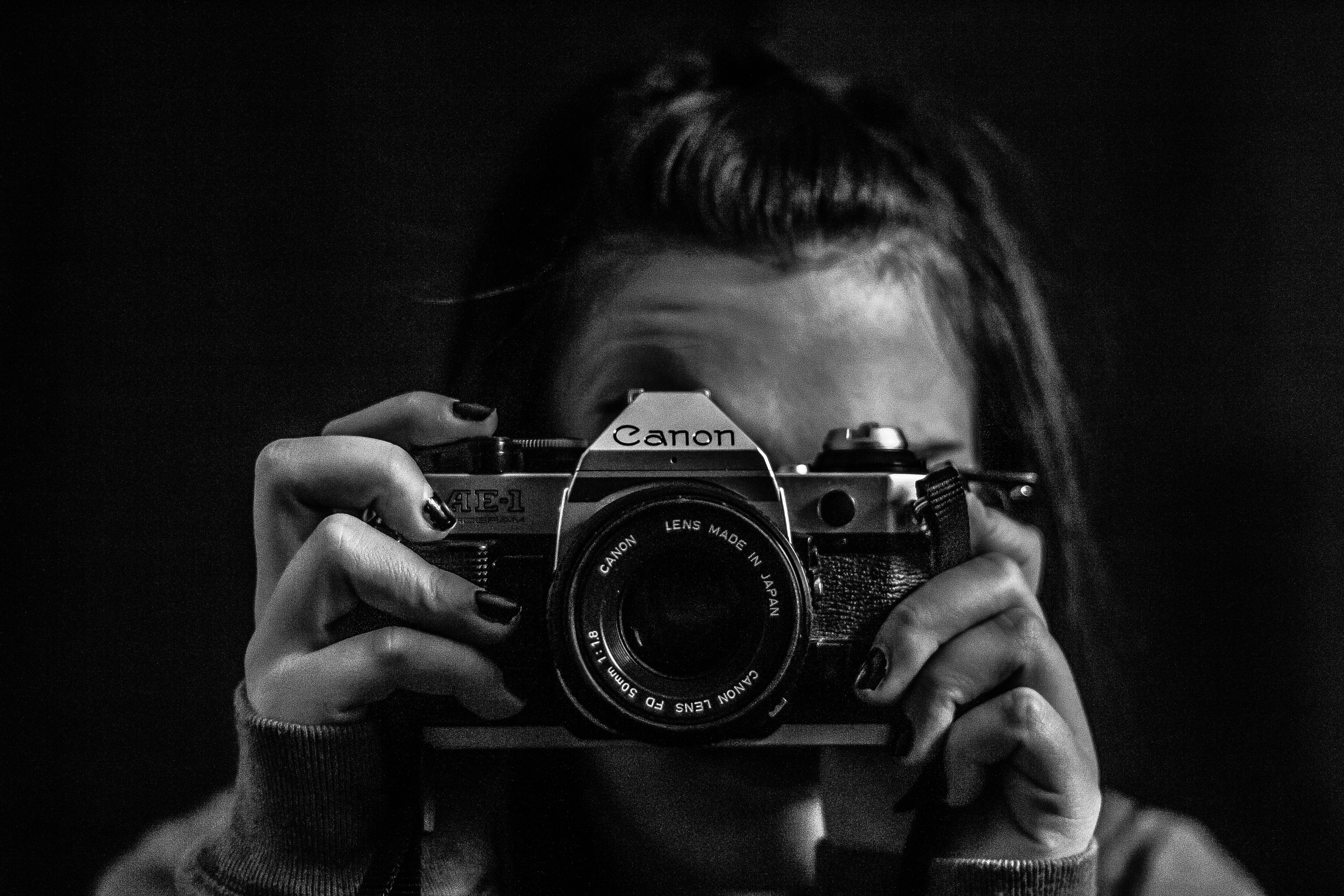 grayscale photo of woman talking photo using Canon camera