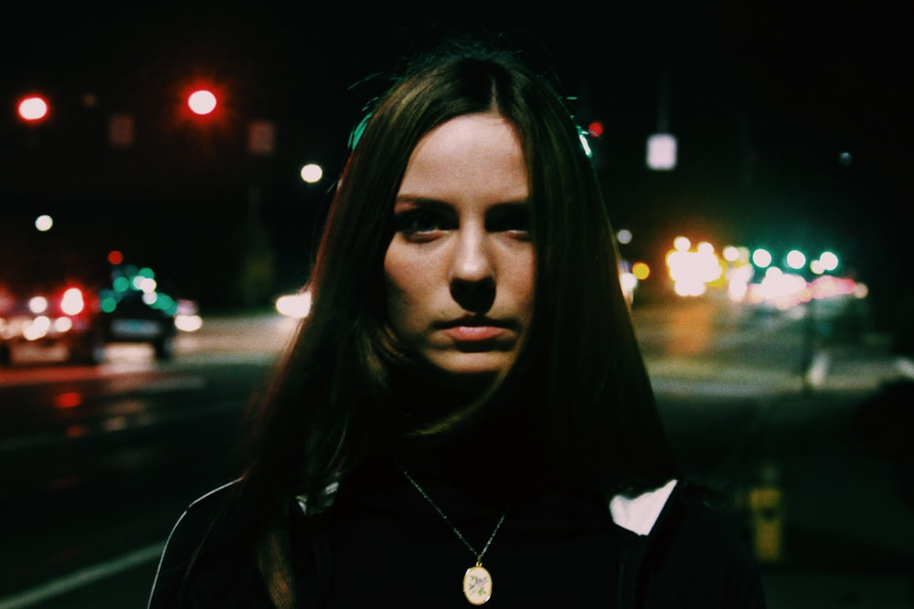 woman standing near city road during nighttime