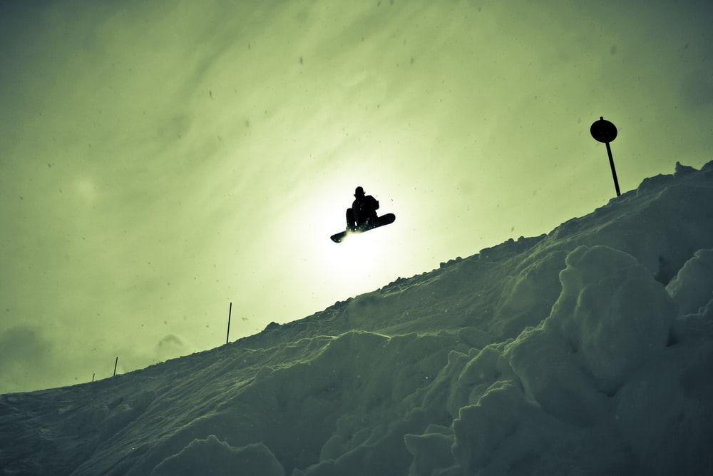 silhouette photography of man creating snowboard stunt