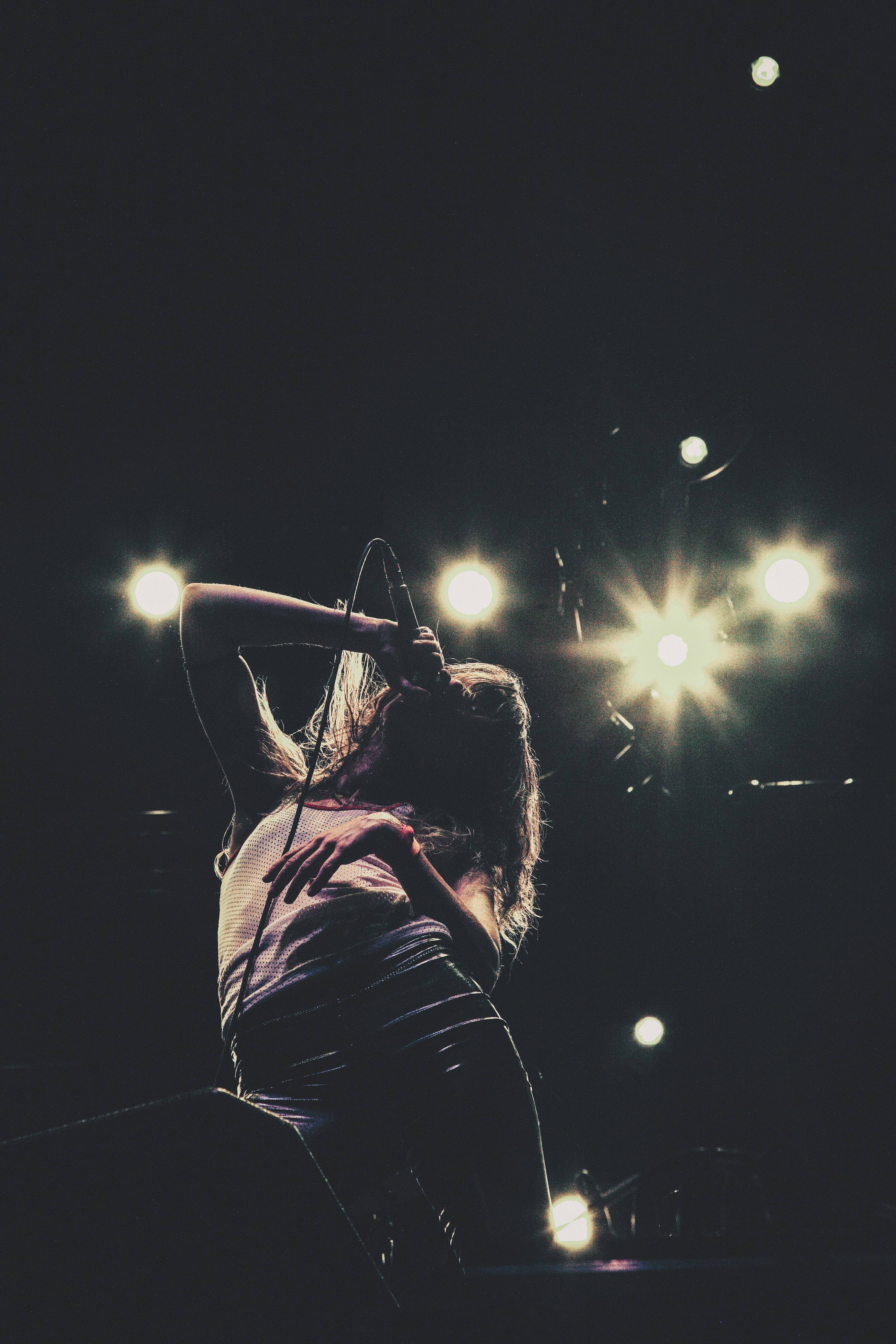 silhoutte of woman holding microphone