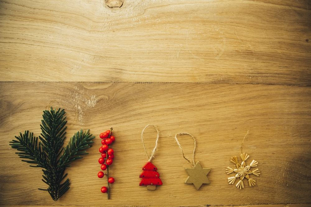 five assorted Christmas tree decors on brown wooden surface