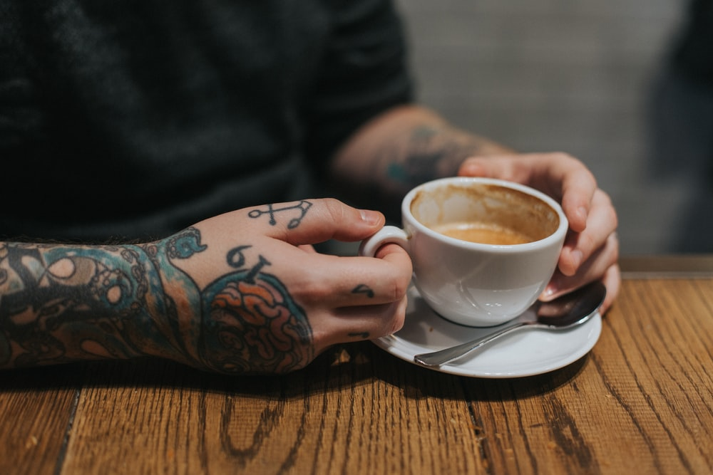 person holding white teacup on white saucer