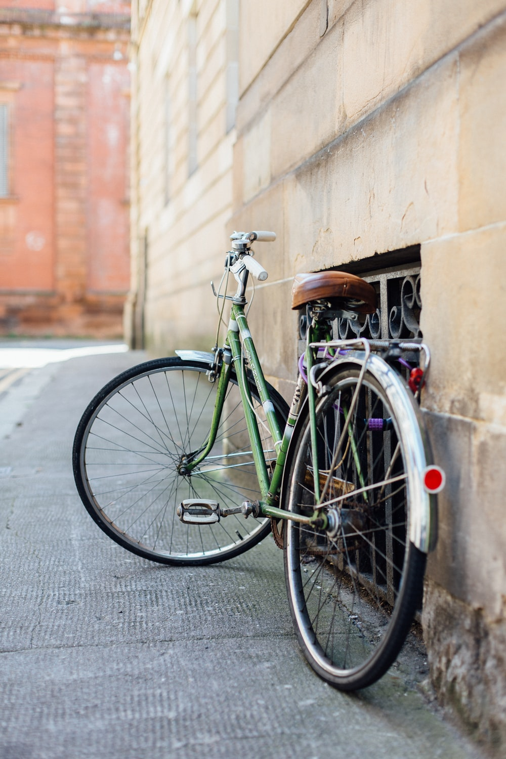 green female beach cruiser bike leaning on wall