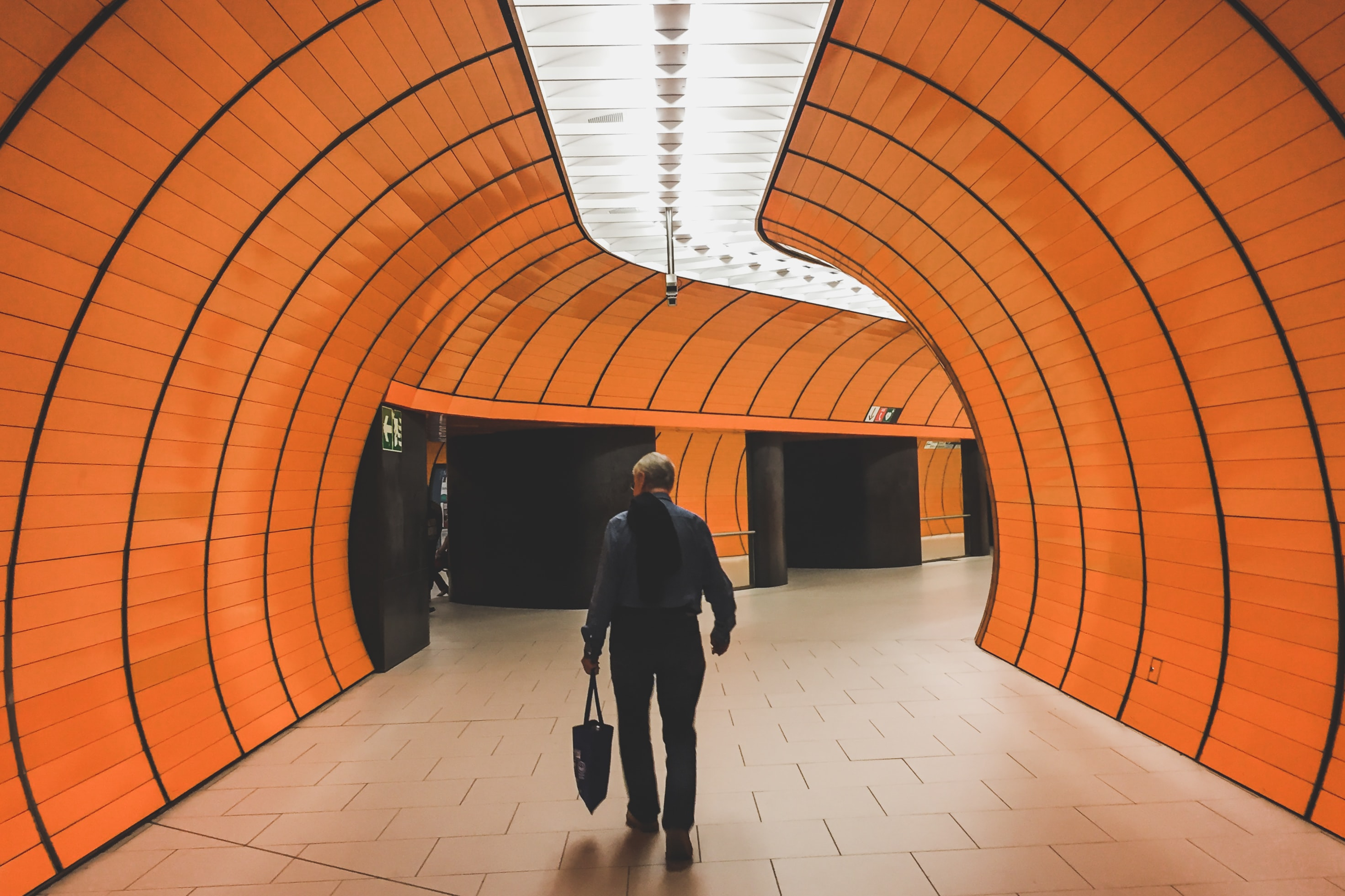 woman walking between orange tunnel building