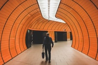 woman walking between orange tunnel building
