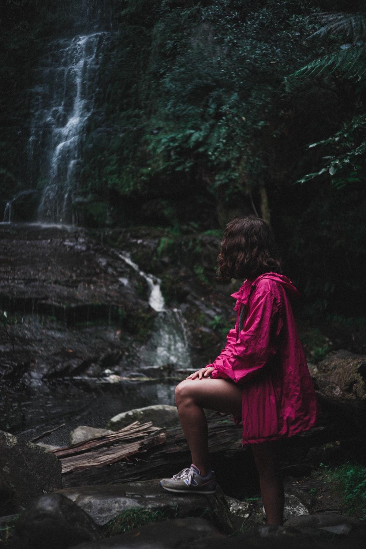 woman in purple jacket standing near waterfalls