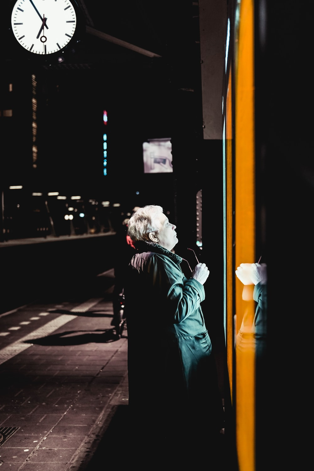 woman staring at the lighted signage at nightime