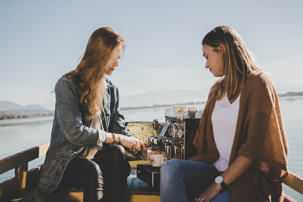two women on boat with espresso machine at sea