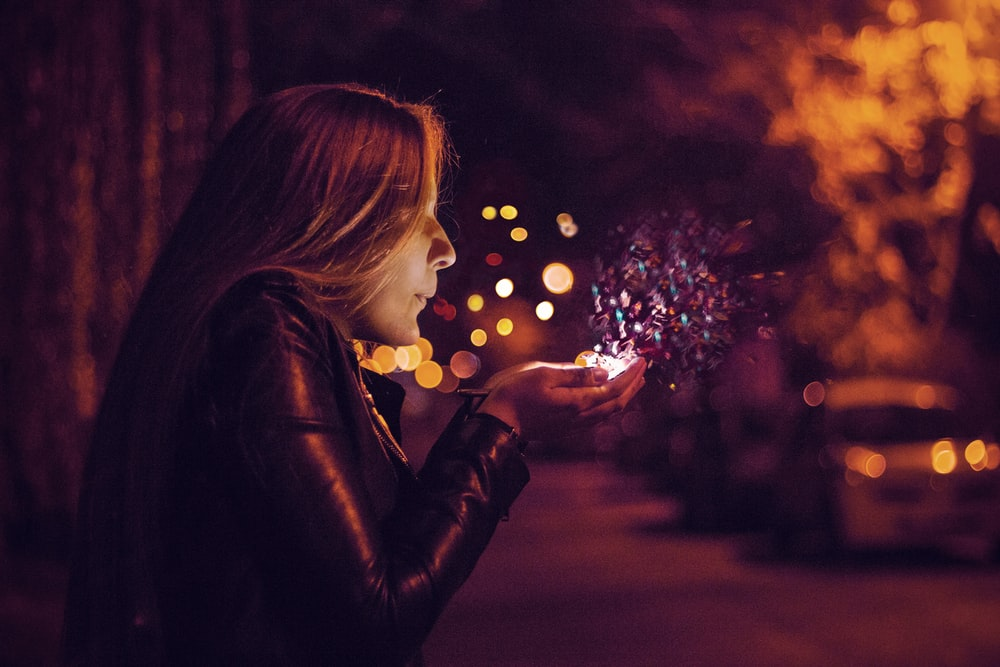 woman blowing sprinkle in her hand