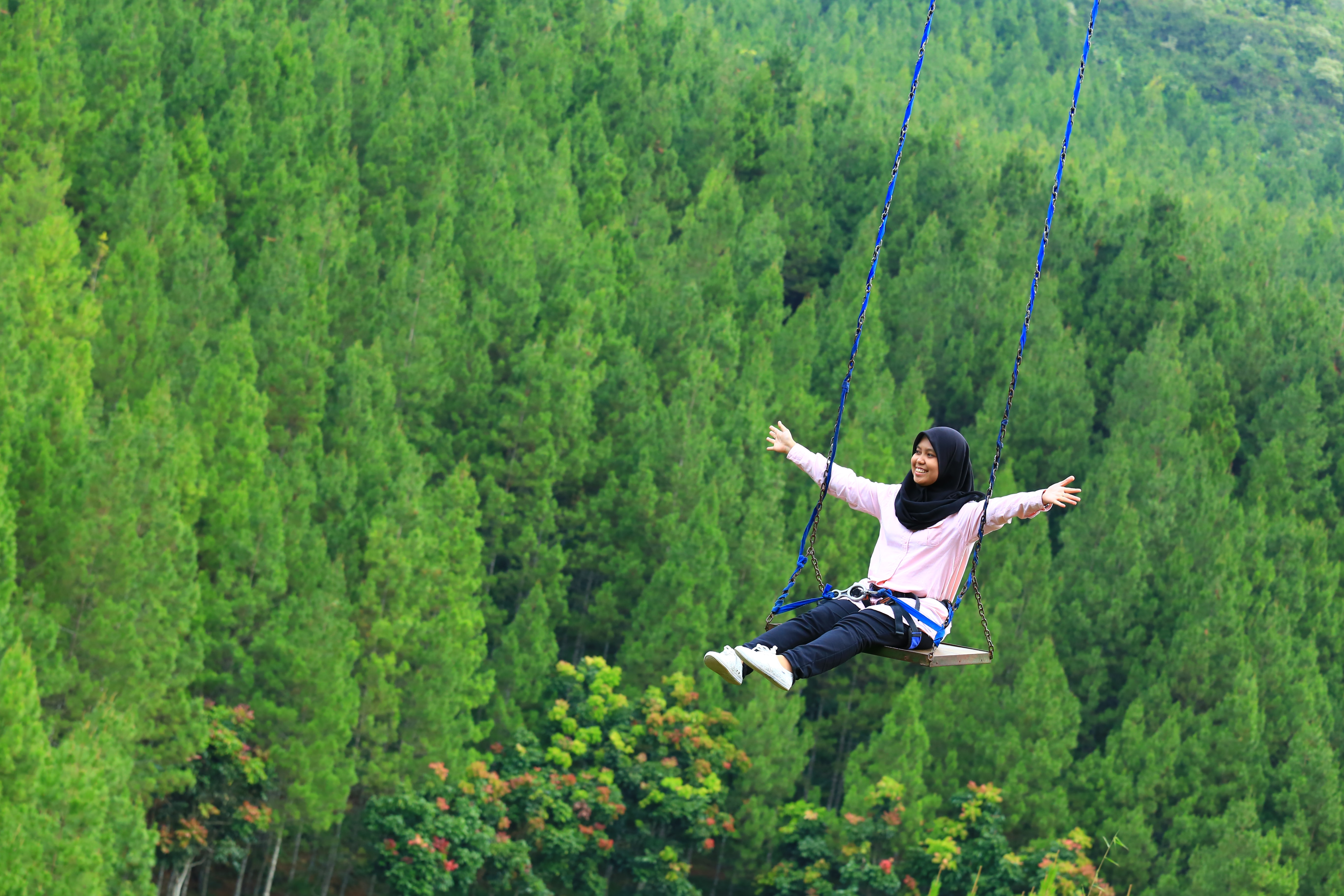 woman with open arms riding swing above green trees at daytime