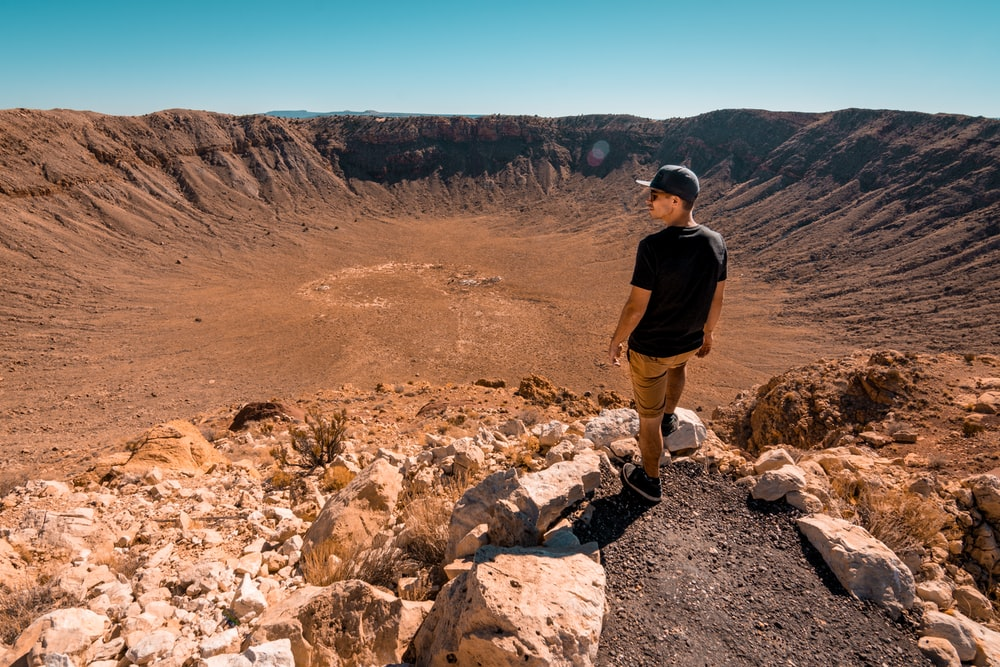 man wearing black shirt standing on rock formation during daytime
