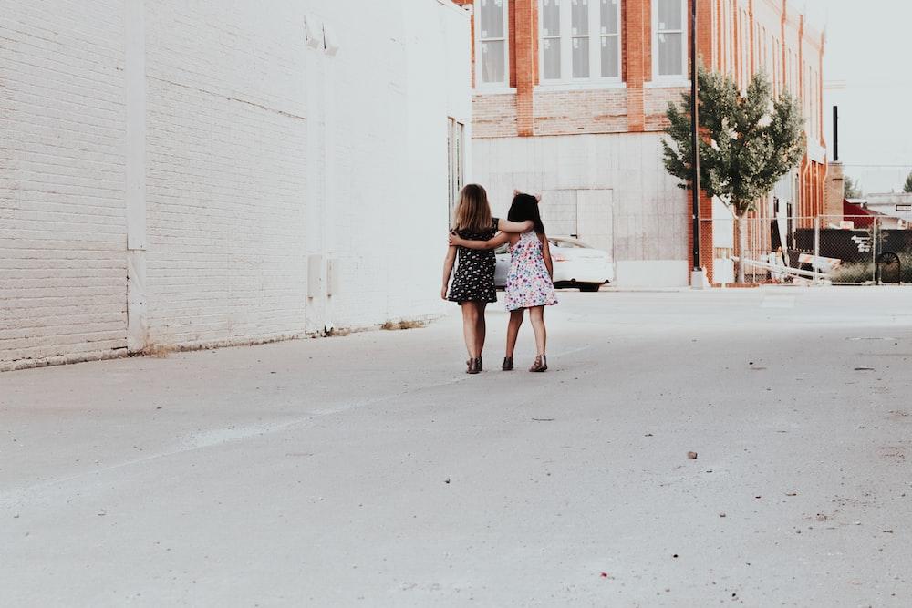 two girls walking on street